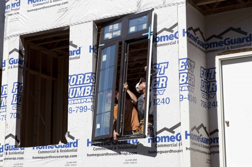 Contractors squeeze in a window into the face of one of the Giles Mini-Mansions.
